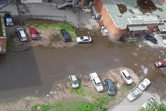 У дома №2 на проспекте Непокоренных лужа превратилась в озеро: Фото