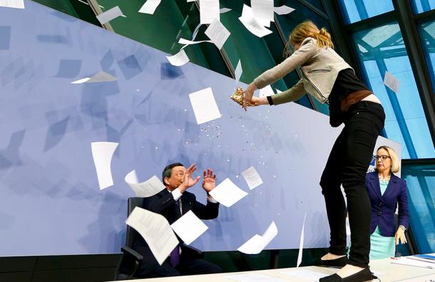 Во время пресс-конференции ЕЦБ Драги на его стол запрыгнула девушка с конфетти
