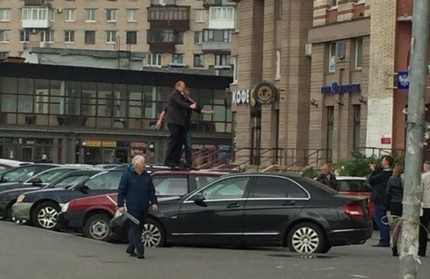 Неадекватные люди ходят по крышам автомобилей возле