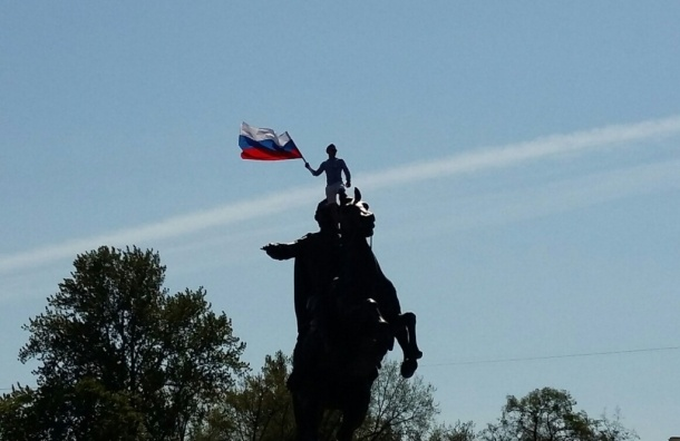 Человек с флагом России оседлал памятник Петру Первому