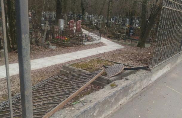 Выбитый машиной люк сломал забор на Большеохтинском кладбище