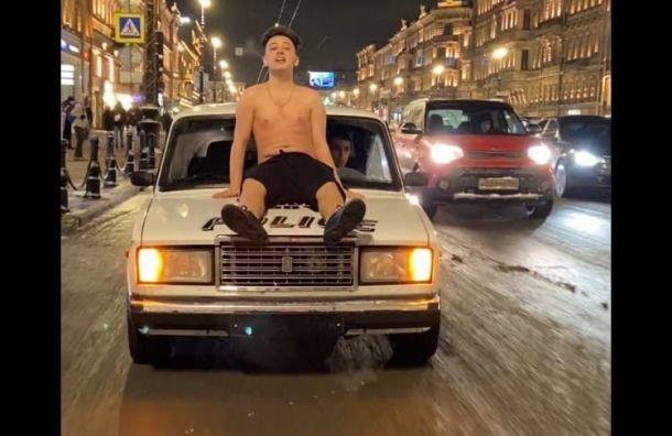 Юноша сголым торсом проехался накапоте машины вцентре Петербурга